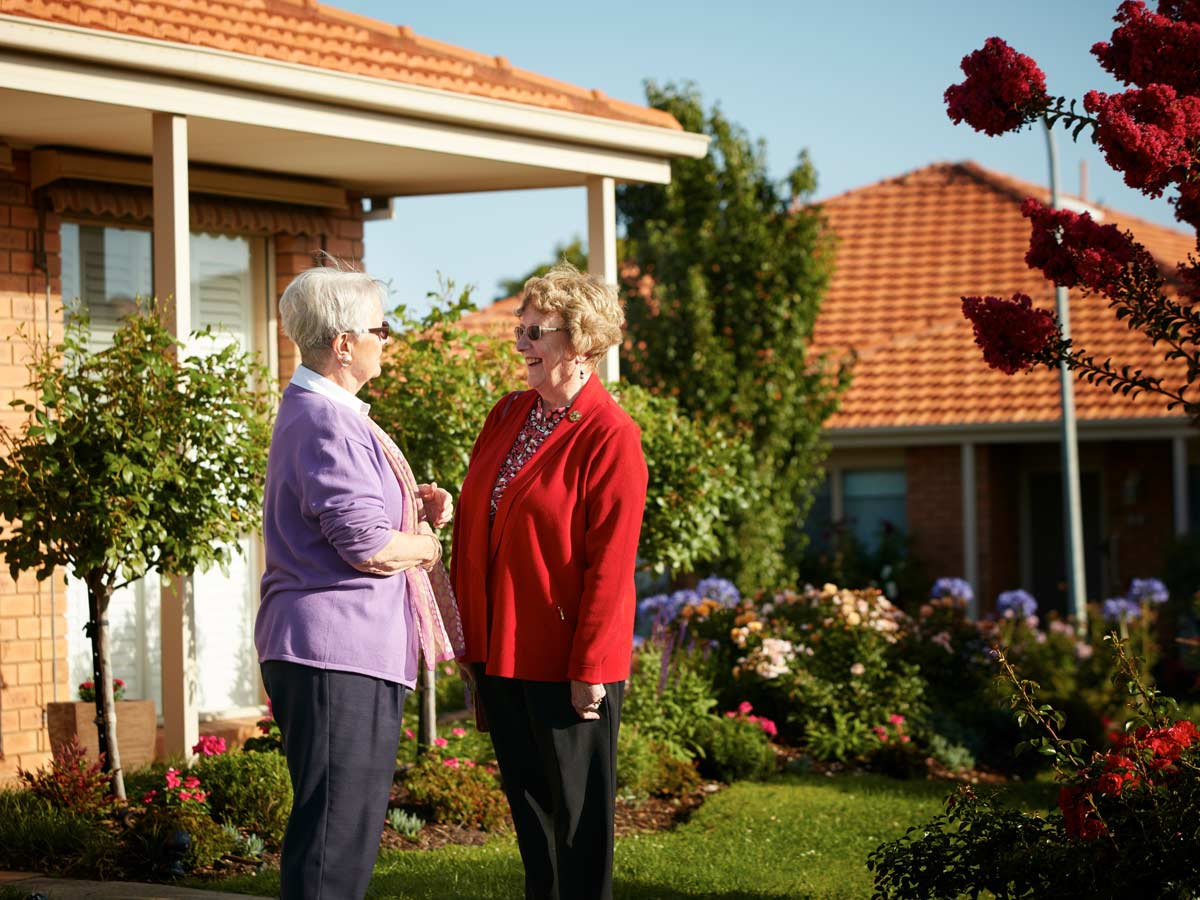 Two women stand chatting in a garden, they both have white hair
