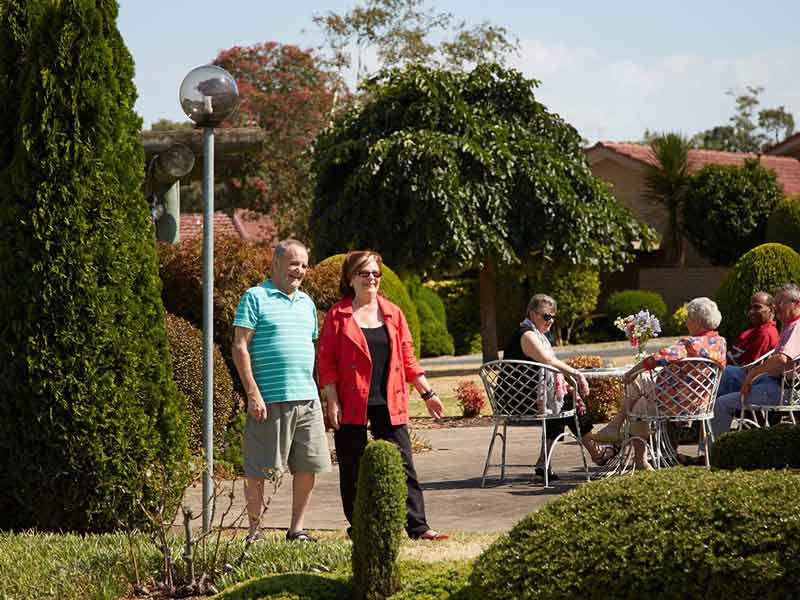 Oak Tree Hill_Village_Couple walking through gardens group in background_external_med res_110214.jpg