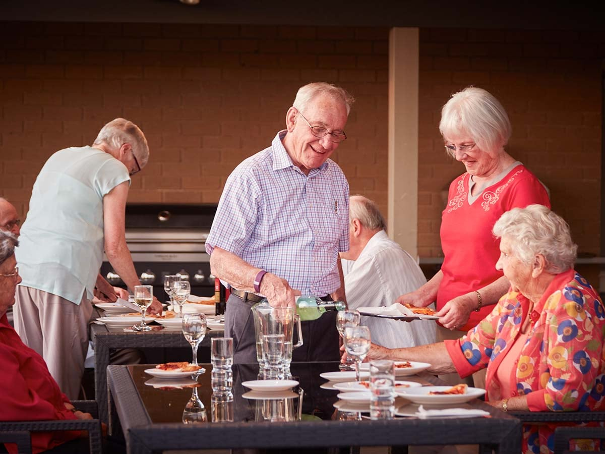 Oak Tree Hill_Village_Group having BBQ dinner in Community Centre BBQ area man pouring drinks_external_high res_170216.jpg