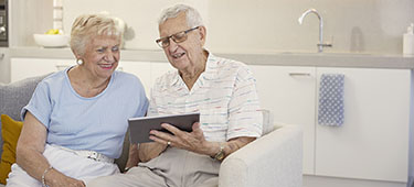 aveo newstead aged care couple looking at tablet 375x170 promo mobile