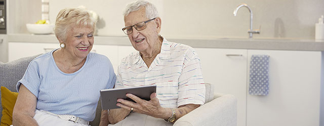 aveo newstead aged care couple looking at tablet 640x250 promo desktop