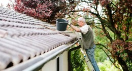 A man stands on a ladder cleaning a roof gutter