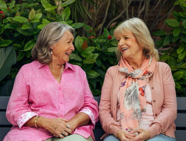 Two ladies sitting on a bench and smiling They are wearing floral clothing in shades of pink
