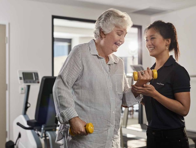 aveo corporate care female resident doing weights with mobile rehab smiling 1200x900 1