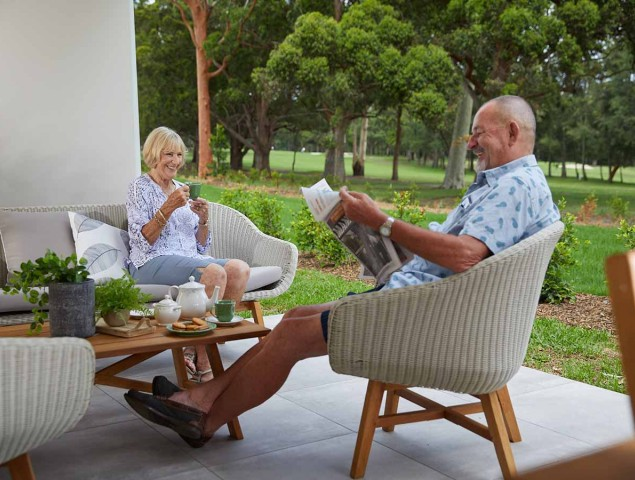 aveo newcastle retirement residents sitting on patio reading newspaper