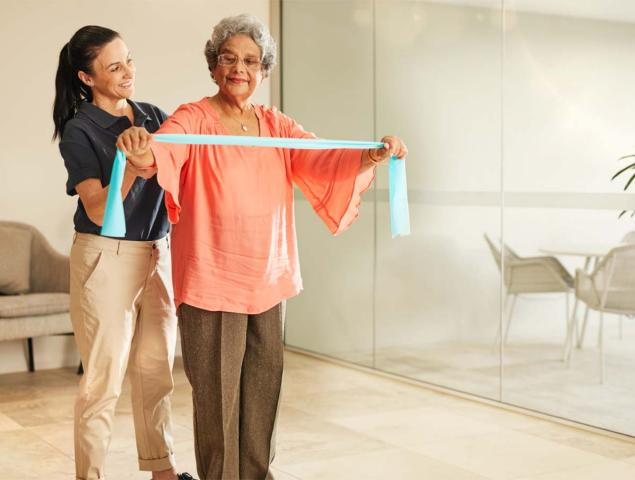 aveo retirement clayfield village physio staff member helping resident do exercises in unit 1200x900